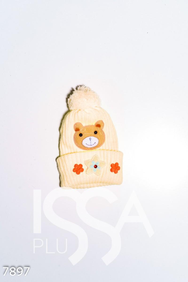 Желтая вязаная демисезонная шапка с аппликациями и помпоном