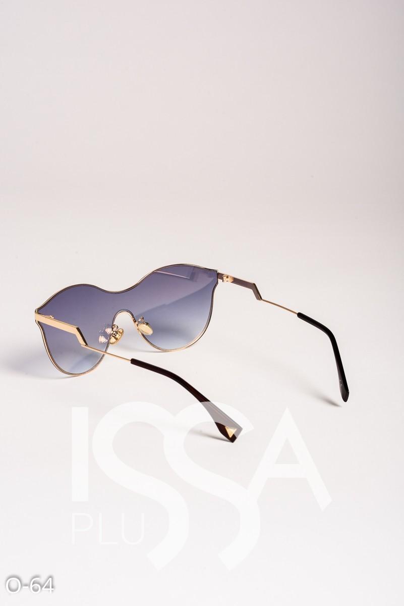 Золотые цельные солнечные очки в фигурной металлической оправе
